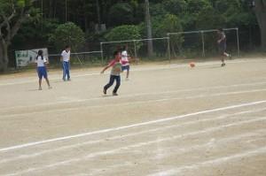 教務主任の榎本先生,?年生とサッカーをしています。今,蹴ったところです。\