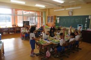 1年生の教室です。子ども達が手を挙げている理由は,「カレー好きな人?」の問いに,「ハーイ」と答えているところです。\