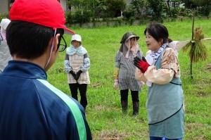 豊津まちづくりセンターの館長さんから稲刈りのコツを教えていただいています。\