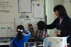 カワイイ1年生の「係活動」引継の風景です。2学期の女の子から3学期は男の子になります。担任も付き添って,仕事の確認をしています。\